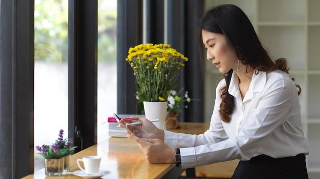 カフェに座ってデジタルタブレットを使用してデジタルを使用して女子学生の側面図