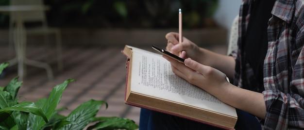 スマートフォンを使用して庭で本を読みながら情報を検索する女子学生の側面図