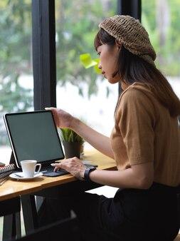 Вид сбоку студентки, работающей с цифровым планшетом на деревянном баре в кафе