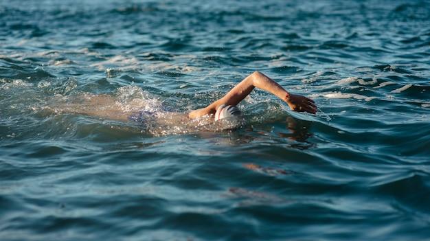 水で泳ぐ女性スイマーの側面図