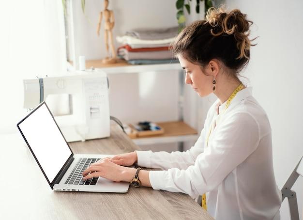 Женский портной с помощью ноутбука, вид сбоку