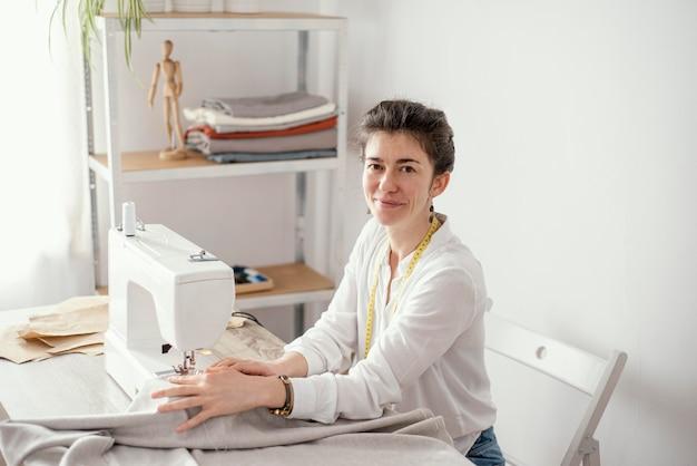 Женский портной, работающий в студии со швейной машиной, вид сбоку