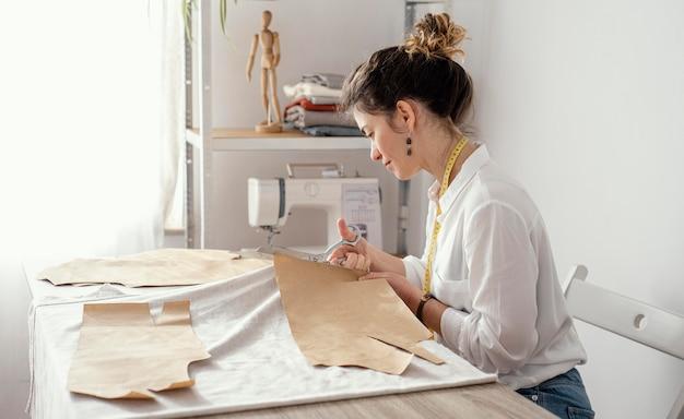 Женский портной, работающий в студии, вид сбоку