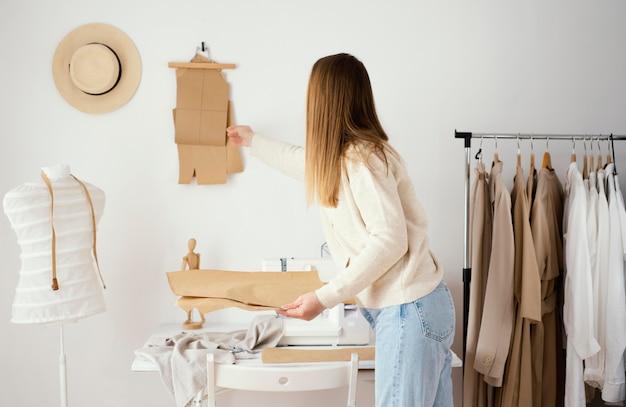 Женский портной, работающий над выкройками в студии, вид сбоку