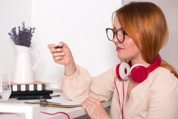 Вид сбоку учительницы в очках, проводящей онлайн-класс