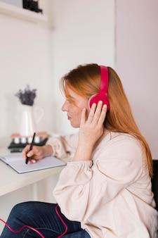 Учительница с наушниками, держащая онлайн-курс, вид сбоку
