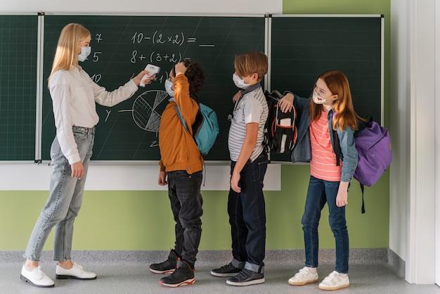 Вид сбоку на учительницу с медицинской маской, проверяющую температуру ученика в школе