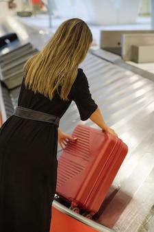 Женщина-путешественница берет чемодан с конвейерной ленты в зоне выдачи багажа в аэропорту, вид сбоку