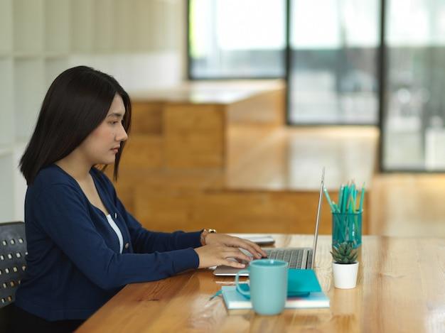 Вид сбоку студентки университета, выполняющей задание с ноутбуком и канцелярскими принадлежностями в библиотеке
