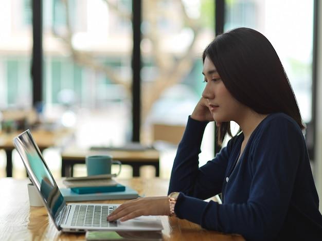 Вид сбоку студентки университета, выполняющей задание с ноутбуком в библиотеке