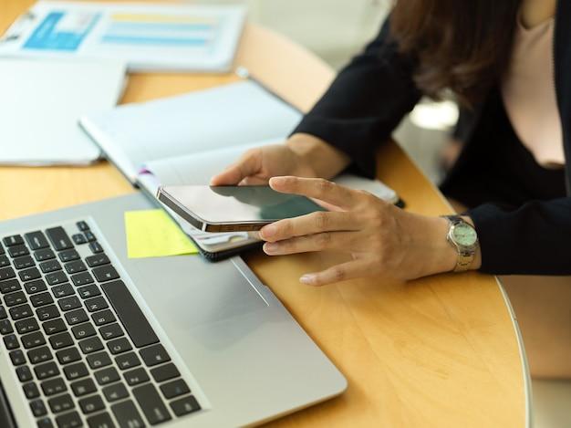 사무실 방에서 노트북으로 작업하는 동안 그녀의 손에 스마트 폰을 사용하는 여성의 측면보기