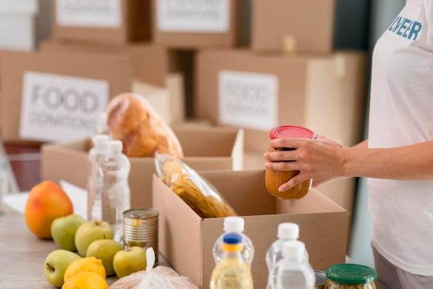 食品寄付と女性ボランティアの梱包箱の側面図