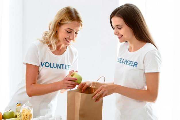 Вид сбоку на женщин-добровольцев, готовящих еду для пожертвования
