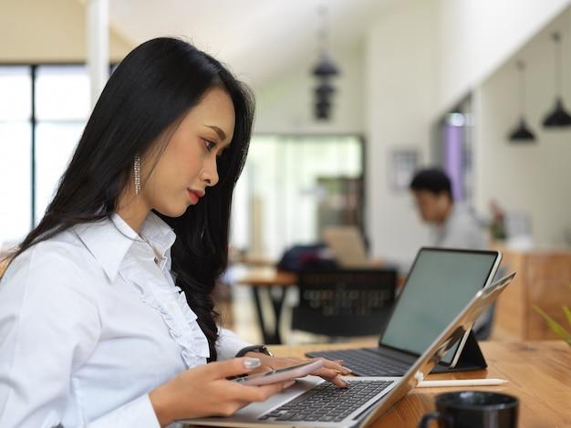 Вид сбоку на работницу, работающую с ноутбуком, планшетом и смартфоном в совместной рабочей среде