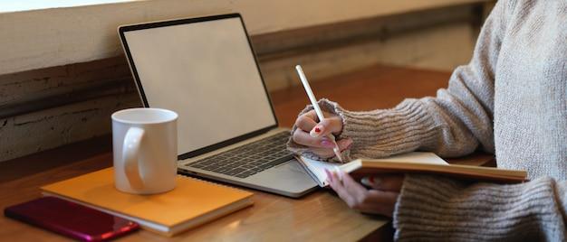 ノートパソコンとスマートフォンのモックアップと木製の作業テーブルに座りながら空白のノートを書いていない女性の側面図