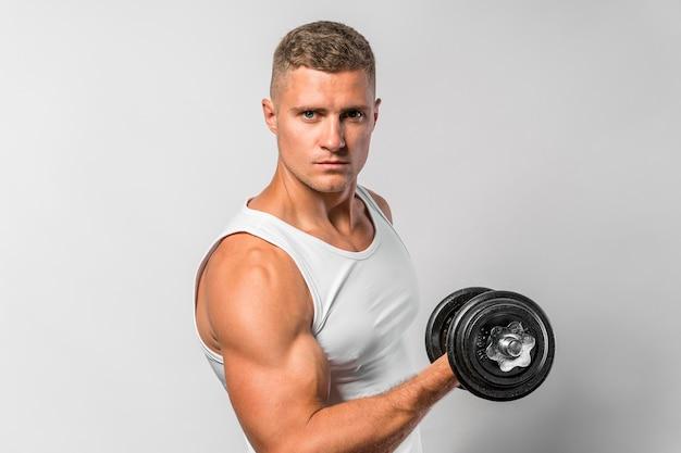 Вид сбоку здорового человека, тренирующегося с весом