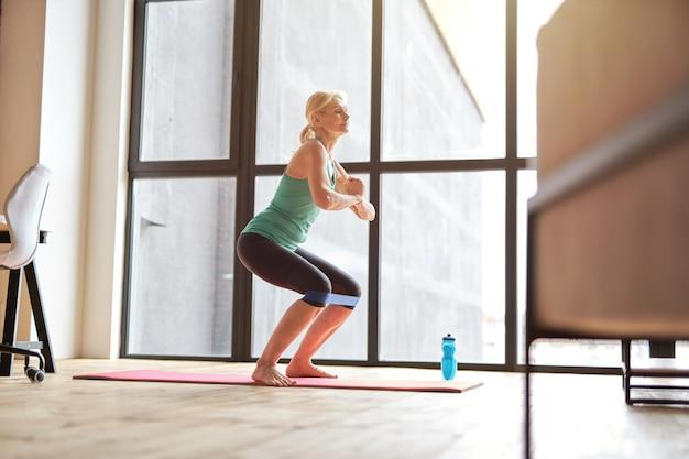 抵抗バンドを使用して自宅で運動するアクティブなライフスタイルをリードするフィット成熟した女性の側面図