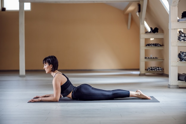 Вид сбоку подходящей женщины йога с каштановыми волосами в позе йоги сфинкса. интерьер студии йоги.