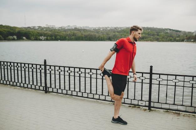 Вид сбоку на подтянутого молодого мужчины в красной рубашке с наушниками и чехлом для смартфона на руке, стоящего на берегу реки и растягивающегося перед упражнениями