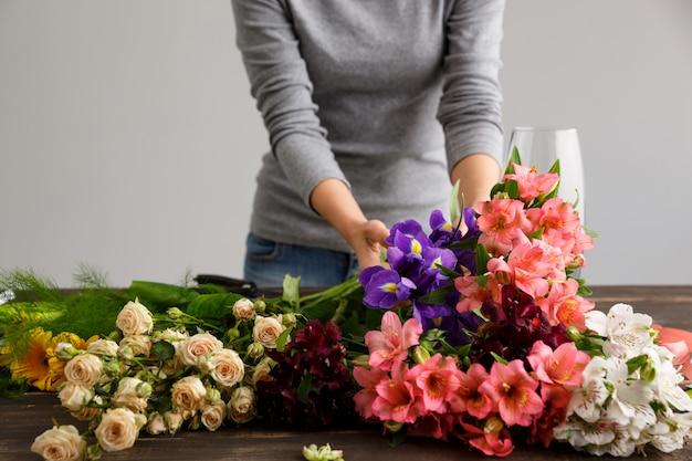 Вид сбоку цветов, флорист в процессе изготовления букета