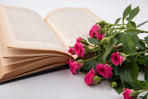 Вид сбоку цветов с открытой книгой на белом фоне