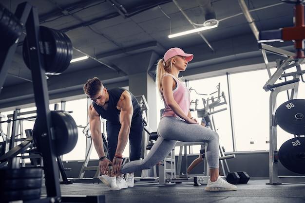 Вид сбоку сосредоточенной и целеустремленной спортивной молодой блондинки в спортивной одежде, выполняющей упражнения для ног, в то время как красивый мускулистый личный тренер следит за ней в тренажерном зале