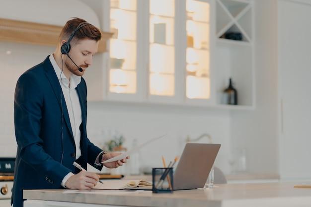 Вид сбоку сосредоточенного бородатого бизнесмена в официальной одежде, работающего удаленно дома, стоящего в помещении и держащего отчет о продажах, пишущего заметки во время онлайн-конференции с коллегами