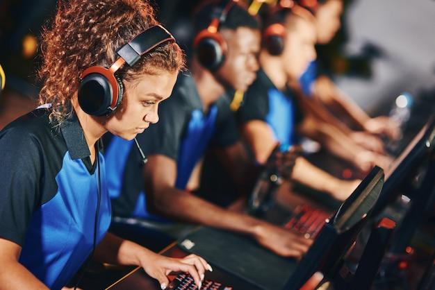 Esportトーナメントに参加し、他のチームメンバーと並んで座って、オンラインビデオゲームをプレイしているヘッドフォンを身に着けている集中した女性のサイバースポーツゲーマーの側面図