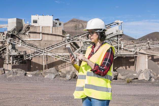Вид сбоку сосредоточенной женщины-инженера в каске и жилете, проверяющей информацию на планшете, стоя возле промышленного объекта строительной площадки