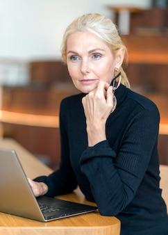 Вид сбоку сосредоточенной пожилой женщины в очках, работающей на ноутбуке