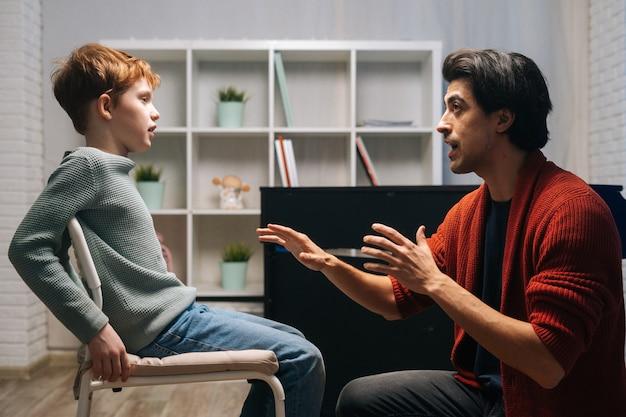 Вид сбоку сосредоточенного школьника, сидящего на стуле и слушающего молодого учителя музыки, говорящего и жестикулирующего