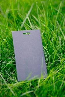 緑の春の草とロゴのコピースペースで販売のためのラベルのない1つの黒いタグで作られたフレームの側面図。自然な概念。