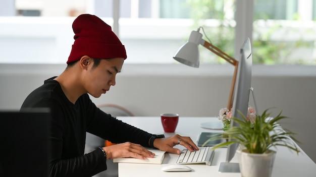 Вид сбоку внештатного графического дизайнера, сидящего на своем рабочем месте и смотрящего на ноутбук во время работы на компьютере.