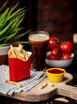 Вид сбоку картофель фри в картонной сумке с кетчупом на деревянной разделочной доске