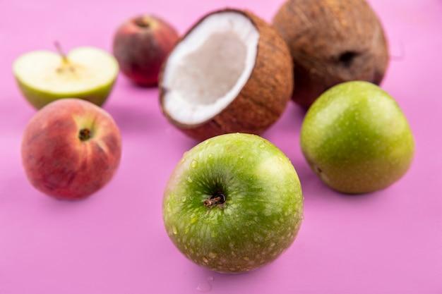 ピンクの表面に分離されたリンゴココナッツなどの新鮮でおいしい果物の側面図