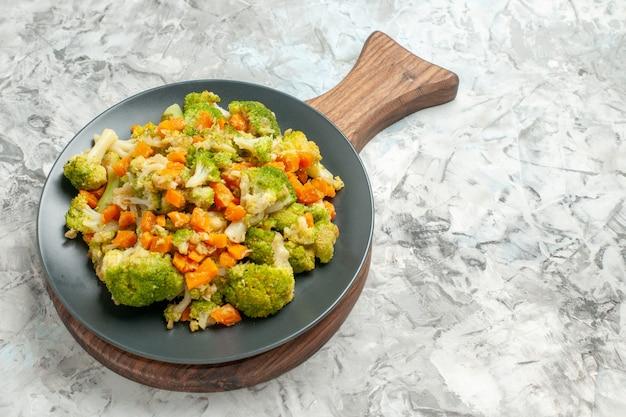 白いテーブルの上の木製まな板に新鮮で健康的な野菜サラダの側面図