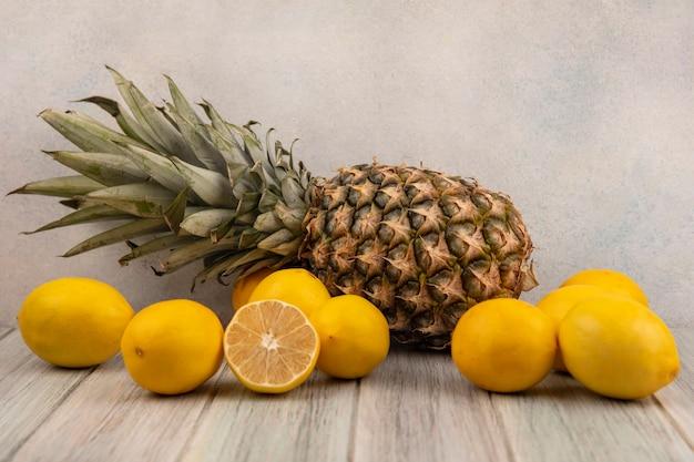 Вид сбоку на свежие и сочные фрукты, такие как лимоны и ананас, изолированные на сером деревянном столе на белом фоне