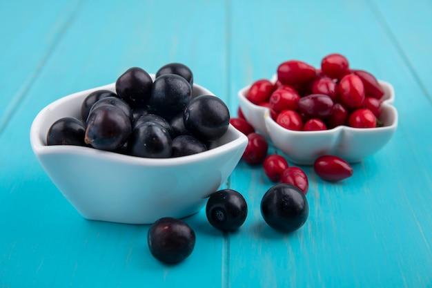 Вид сбоку свежего черного винограда на миске с ягодами кизила на синем деревянном фоне