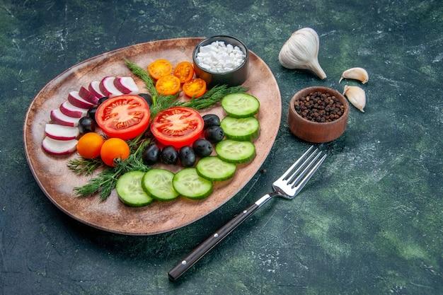 茶色のプレートに新鮮なみじん切り野菜オリーブと緑黒の混合色の背景にフォークペッパーニンニクの側面図
