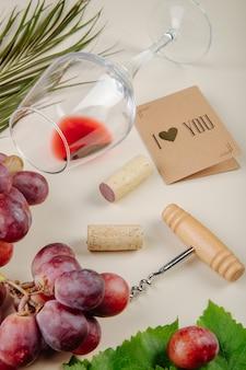 新鮮なブドウ、小さなポストカード、ワインのコルクのボトルスクリュー、白いテーブルの上に横たわるワイングラスの側面図