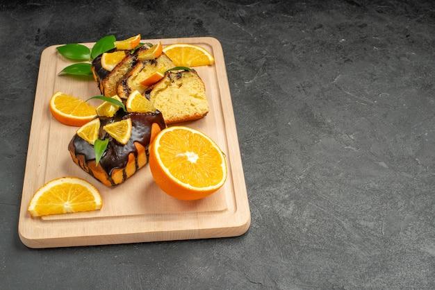 暗いテーブルの上の新鮮なレモンスライスと焼きたての刻んだケーキスライスの側面図