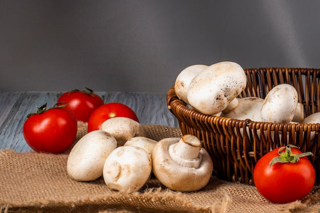 Вид сбоку шампиньонов из свежих грибов в плетеной корзине и свежих помидоров на вретище