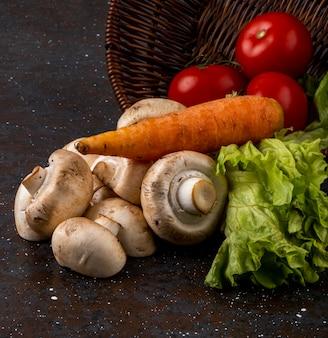 Вид сбоку шампиньонов свежих грибов со спелыми овощами, разбросанными из плетеной корзины на темном фоне