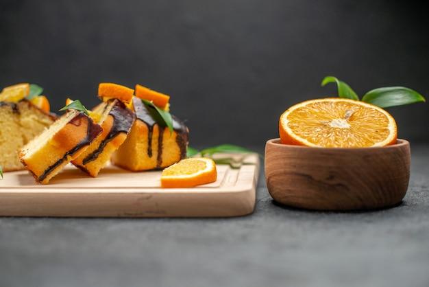 暗いテーブルの上の新鮮なオレンジスライスと焼きたての刻んだケーキスライスの側面図