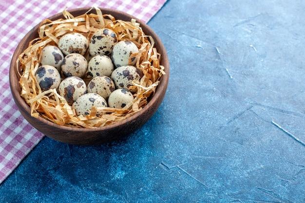 파란색 배경의 오른쪽에 있는 보라색 벗겨진 수건에 있는 갈색 그릇에 있는 조직 바구니에 있는 신선한 가금류 닭 농장 달걀의 측면 보기