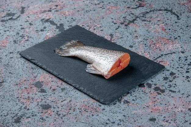 여유 공간이있는 블루 블랙 믹스 색상 테이블에 어두운 색상 트레이에 신선한 생선의 측면보기