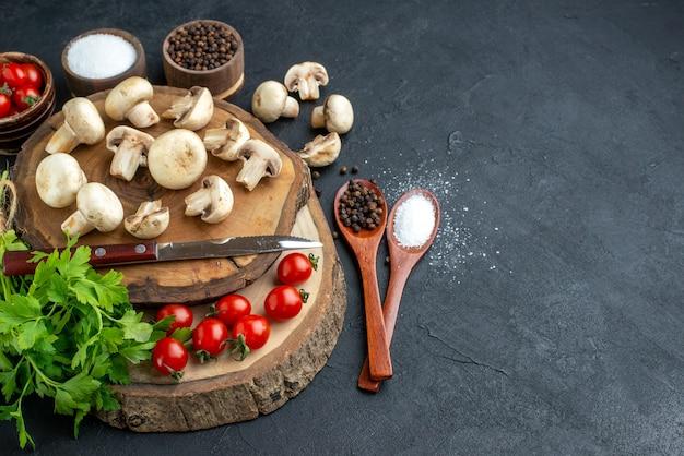 黒の背景に木の板タオルに新鮮な生のキノコと緑のバンドルナイフトマトスパイスの側面図