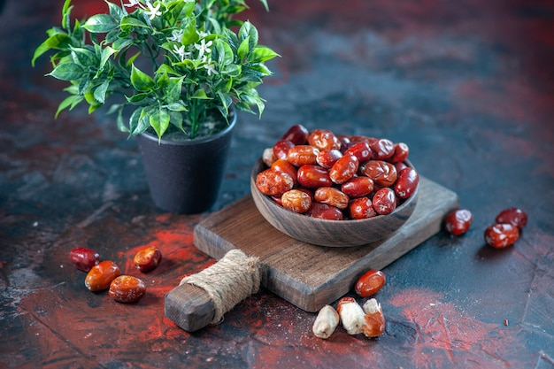 Вид сбоку свежих сырых плодов малины в миске на деревянной разделочной доске и цветочном горшке на фоне смешанных цветов