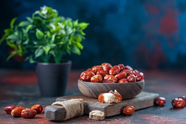 Вид сбоку свежих сырых плодов малины в деревянной миске на разделочной доске и цветочном горшке на фоне смешанных цветов