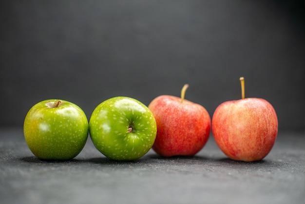 暗いテーブルで健康的な生活の一部として新鮮な赤と緑のリンゴの側面図